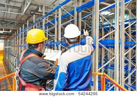 two warehouse worker in front of rack stack in storehouse