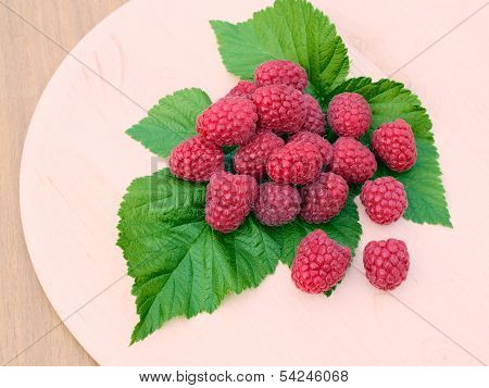 Raspberries Are On A Round Wooden Board