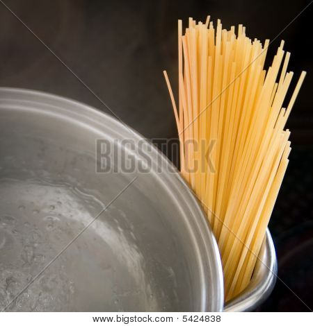 Dry Spaghetti With Boiling Water And Dark Background