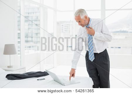 Side view of a mature businessman wearing tie while using laptop at a hotel room