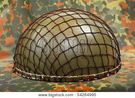 Retro military helmet ( paratrooper's helmet) on a camouflage background.