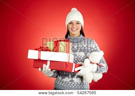 Portrait of happy girl with stack of giftboxes and teddybear looking at camera