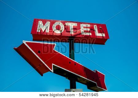 A vintage red neon hotel sign with a red arrow and a sky blue background