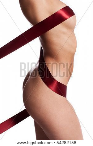 Red ribbon artistically wound around a naked female body concealing the nipple and accentuating the womans curves and sexy buttocks, side view of the torso isolated on white
