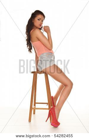 Beautiful leggy woman in stilettos and sexy skimpy shorts posing sitting sideways on a wooden bar stool giving the camera a sultry seductive look, isolated on white