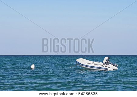 Anchored Dinghy On Sea With Blue Sky.