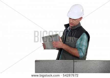 Man placing brick on unfinished wall