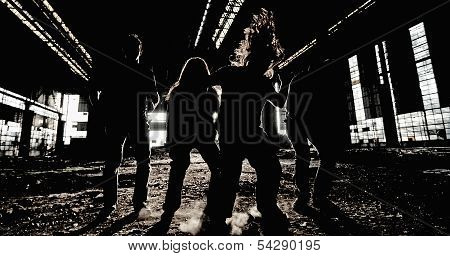 Rock band group photo in an abandoned industrial hall