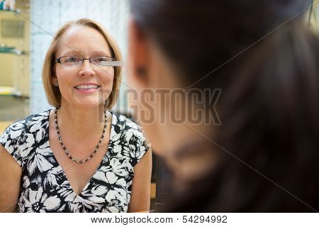 Optician measuring mature woman's eyeglasses in store