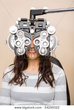 Happy young female patient looking through phoropter during eye exam