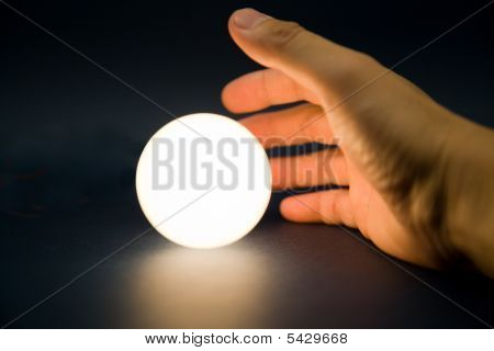 Hand Touching A Bright Ball