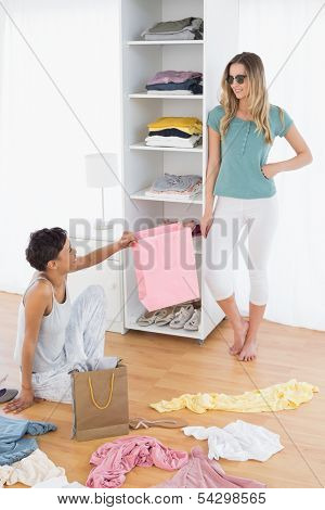 Two happy young women arranging clothes in the shelf at home