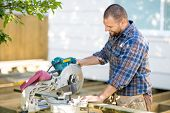 stock photo of sawing  - Happy mid adult carpenter cutting wood using table saw at construction site - JPG