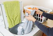 picture of dirty-laundry  - Horizontal photo female hands putting dirty laundry into washing machine - JPG