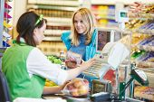 stock photo of grocery cart  - Customer buying food at supermarket and making check out with cashdesk worker in store - JPG