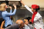 stock photo of flight attendant  - Friendly flight attendant helping passenger to put luggage cabin compartment - JPG