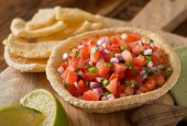 foto of cilantro  - Fresh tomato salsa with serrano pepper red onion green onion lime and cilantro in a tortilla bowl.