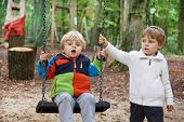 Two Little Sibling Boys Having Fun  In Autumn Forest With Swing