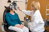 Female optician using phoropter to examine senior woman's eyes