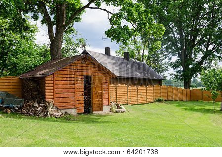 Handmade Woodshed In Village Along Wooden Fence