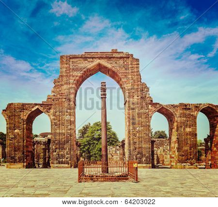 Vintage retro effect filtered hipster style travel image of Iron pillar in Qutub complex - metallurgical curiosity.  Qutub Complex, Delhi, India