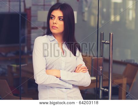 Portrait of a thinking young woman looking away in office