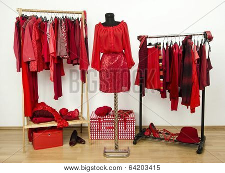 Dressing closet with red clothes arranged on hangers and an outfit on a mannequin.