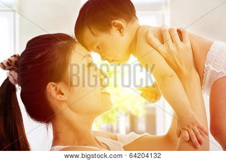 Happy  Mother Holding Adorable Child Baby With Sunrise Background