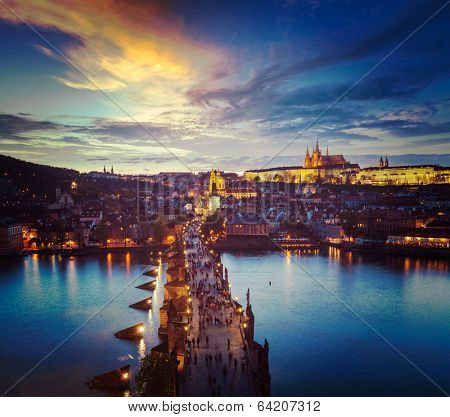 Vintage retro hipster style travel image of night aerial view of Prague castle and Charles Bridge over Vltava river in Prague, Czech Republic. Prague, Czech Republic