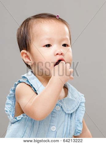 Baby girl put finger into mouth