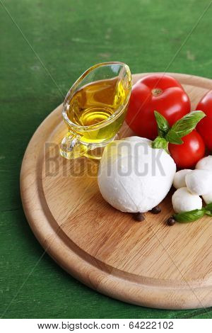 Composition with tasty mozzarella cheese balls, basil and red tomatoes, olive oil on cutting board, on color wooden background