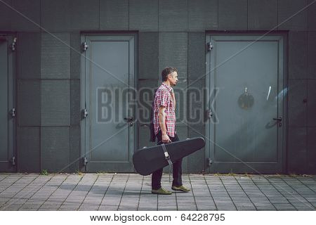 Man In Short Sleeve Shirt Walking With Guitar Case