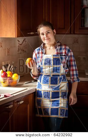 Smiling Housewife Holding Orange