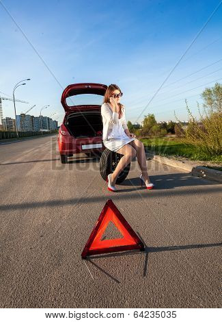 Woman Sitting On Spare Wheel Against Of Broken Car