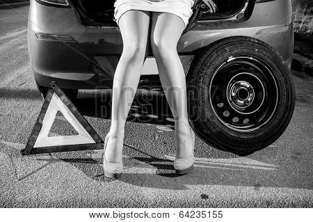 Woman Sitting On Broken Car Near Warning Sign And Spare Wheel