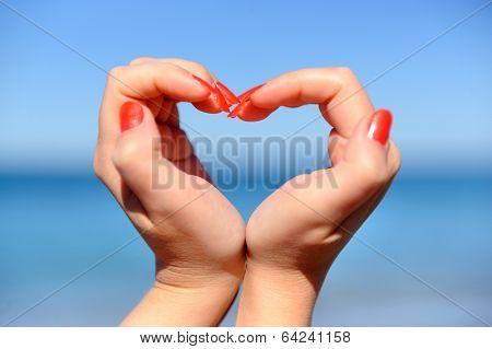 Female Hand Making A Heart Shape Against