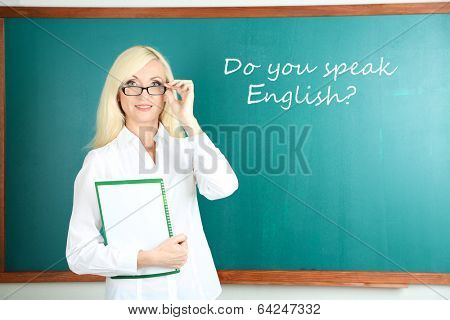 School teacher near blackboard in classroom