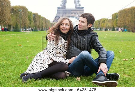 Young Romantic Couple Sitting Near The Eiffel Tower
