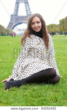 Beautiful Young Woman In Polka Dot Trench Sitting On Grass Near The Eiffel Tower