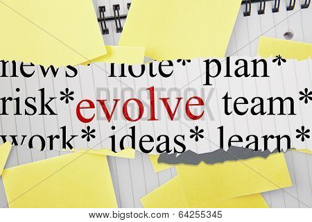 The word evolve against sticky notes strewn over notepad