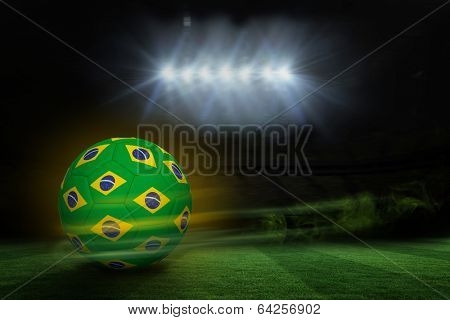 Football in brazilian colours against football pitch under spotlights