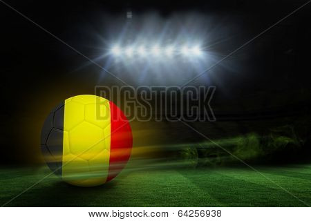Football in germany colours against football pitch under spotlights