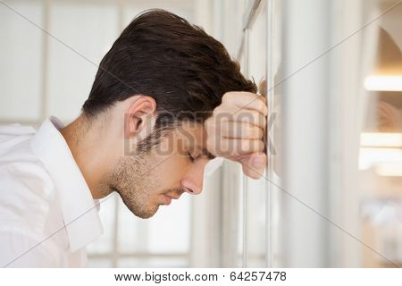 Casual worried businessman leaning against the window in his office