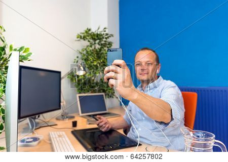 A business man taking a selfie in his clean and paperless office.
