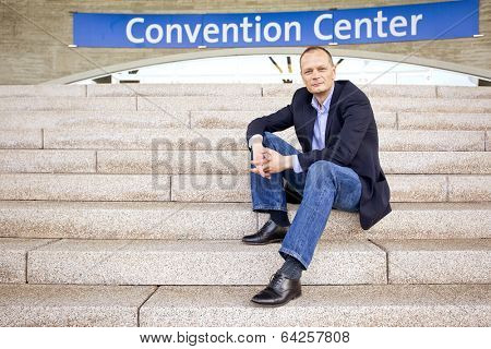 Smart casually dressed attendee, sitting on the steps of a convention center