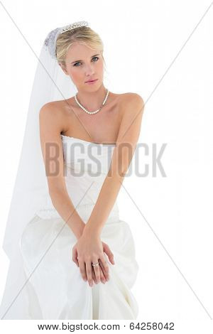 Portrait of beautiful sensuous bride in off shoulder dress sitting against white background