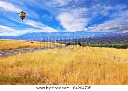 On a picturesque field of multi-colored balloon flies. A field of yellow grass demarcated green alleys