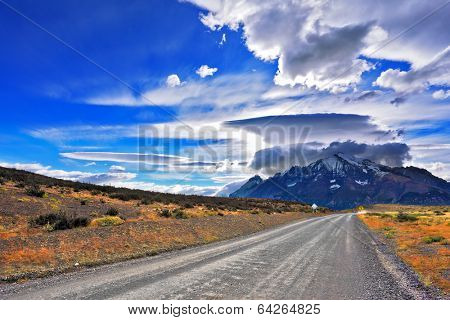 Incredible clouds over the mountain glaciers. Stunning sunset in the Chilean Patagonia. The dirt road leads to the mountain range