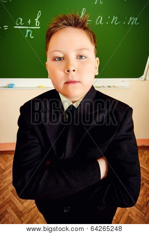 Serious schoolboy in uniform stands near the blackboard at a classroom.