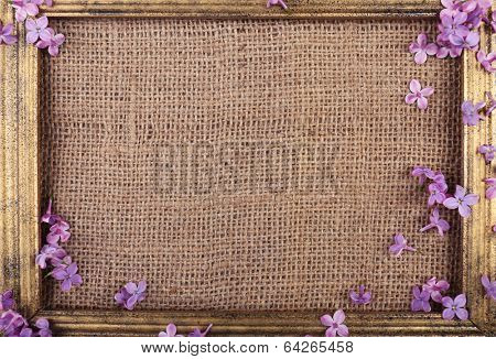 Beautiful lilac flowers and wooden photo frame on burlap background